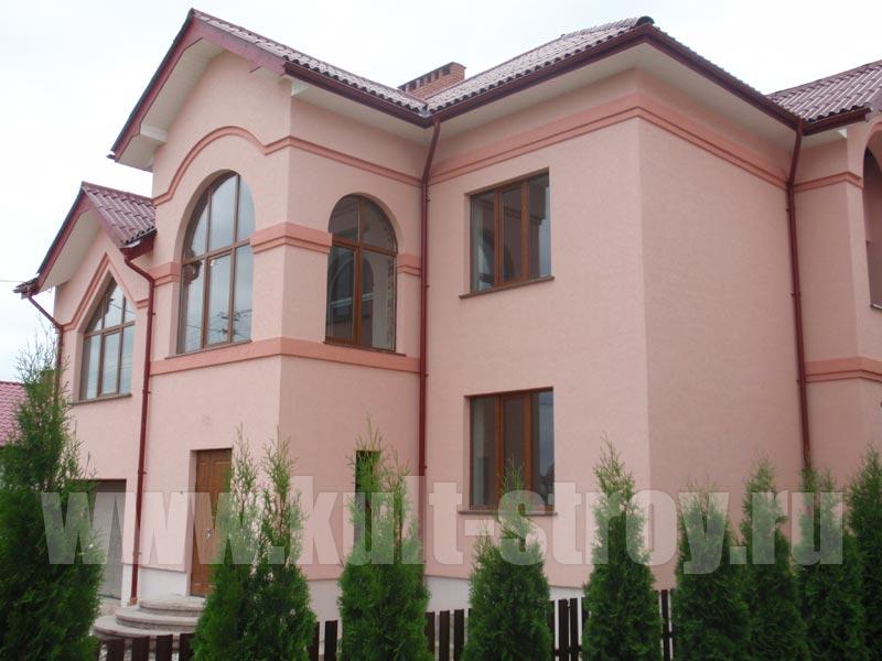 оштукатуренный и покрашенный в розовый цвет дом