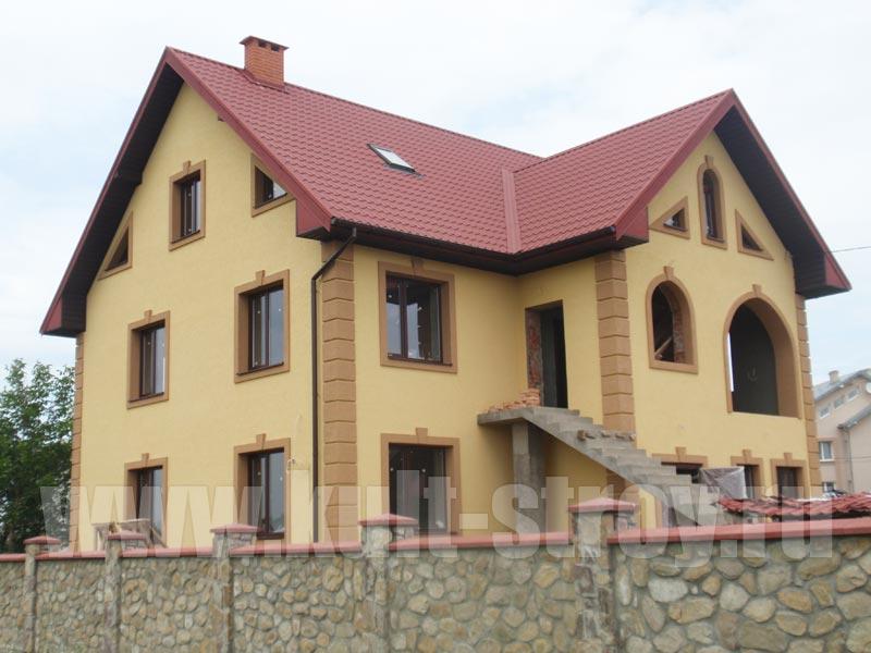 оштукатуренный и покрашенный в желто-бежевый цвет дом