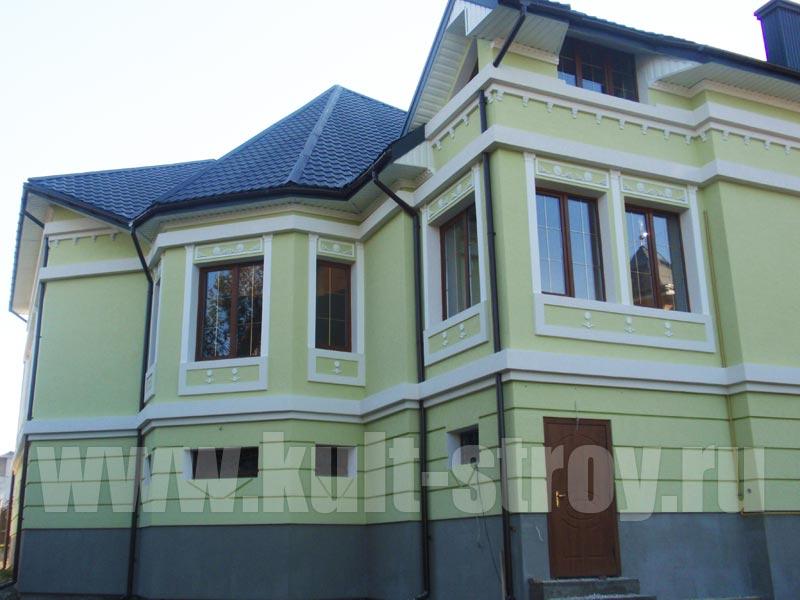 дом с зеленым фасадо и белыми бордюрами